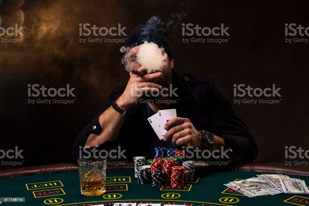 Swell Bearded Man With Cigar And Glass Sitting At Poker Table In A Casino Gambling Playing Cards And Roulette Stock Photo Download Image Now Home Remodeling Inspirations Basidirectenergyitoicom