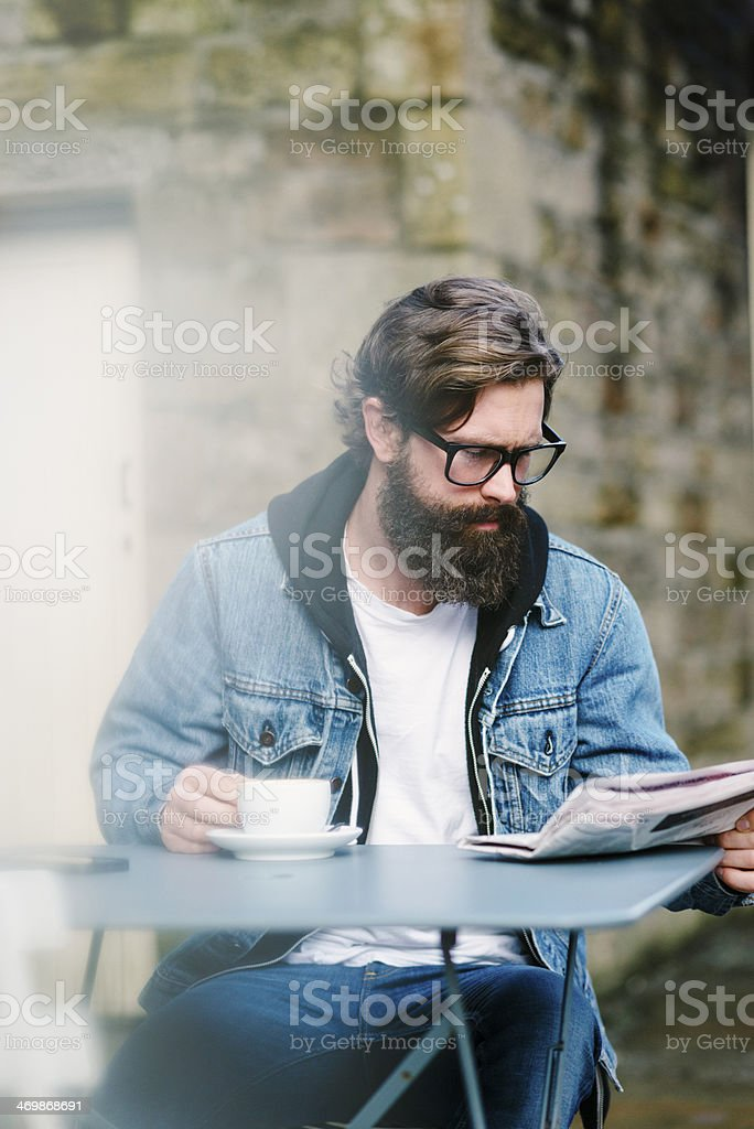 Bearded Man with coffee and newspaper stock photo