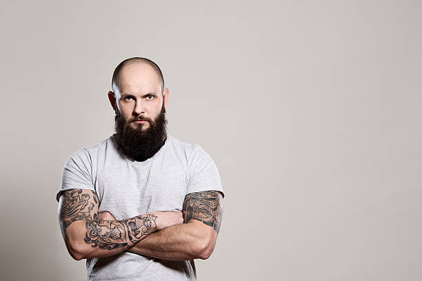 bearded man with crossed arms - tattoo stock photos and pictures