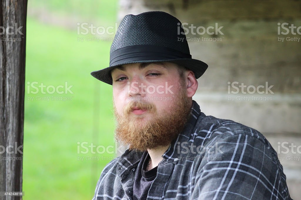 d4cc480ce472c Bearded Man With Fedora Hat Poses For Camera royalty-free stock photo