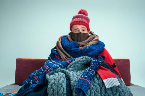bärtiger mann mit schornstein zu hause auf dem sofa sitzen. medizinische konzepte. - erkältung und grippe stock-fotos und bilder