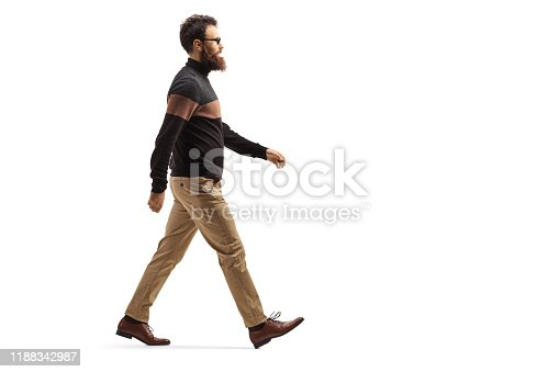 Full length profile shot of a bearded man with glasses walking isolated on white background