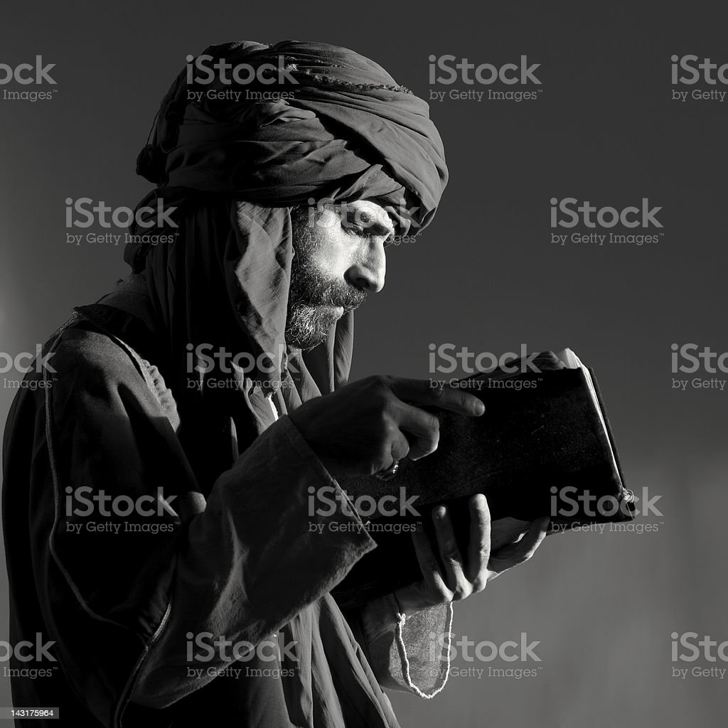 Bearded man with headscarf reading old antique book stock photo