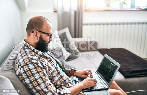 istock Bearded man with laptop working at home trading on exchange 1054655566