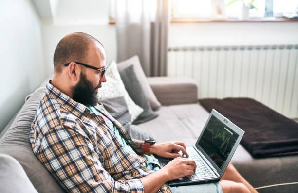 Bärtiger Mann mit Laptop arbeiten im Hause Börsenhandel einsteigen – Foto