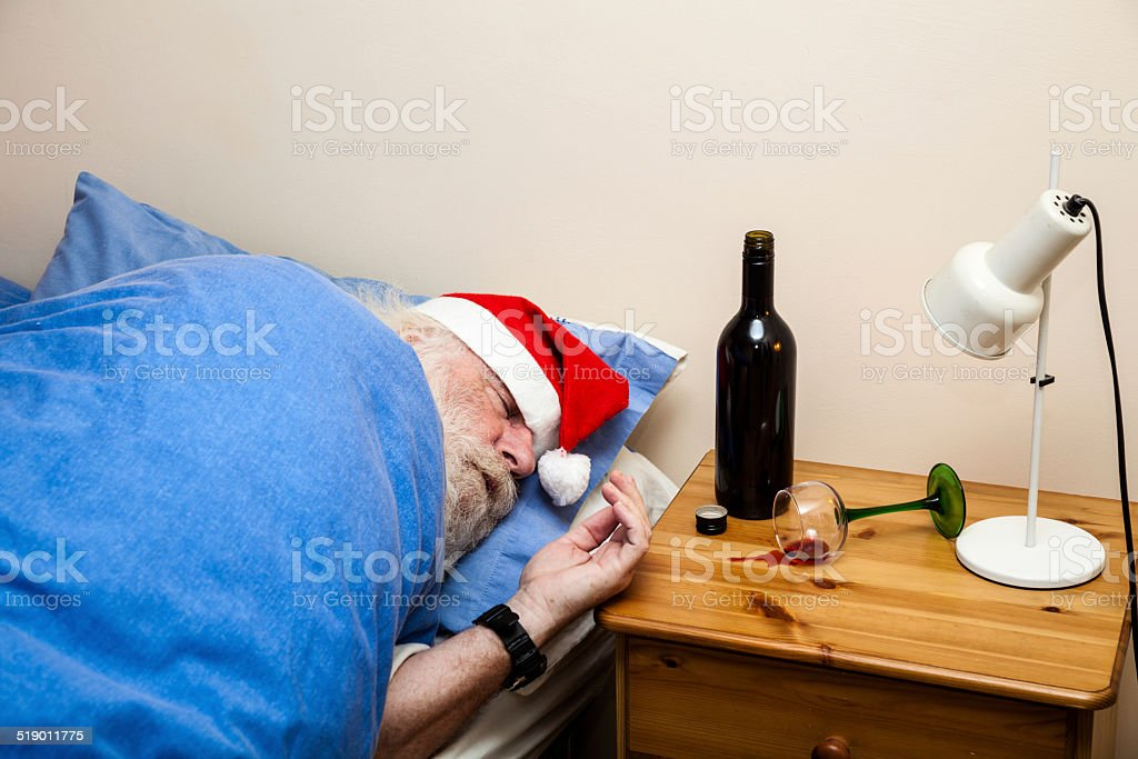bearded man with  santa hat - sleeping off wine hangover stock photo