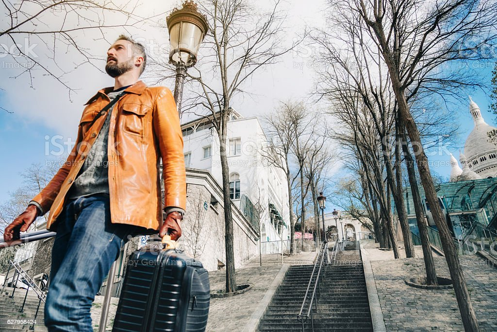 bearded man with suitcase coming down monmartre stairs in paris stock photo