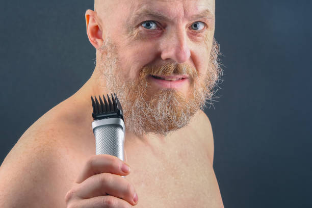 Bearded man with trimmer to adjust beard in hand stock photo