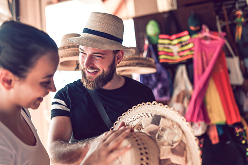 istock Bearded Market Vendor Offering Hat To a Lady 1060907356