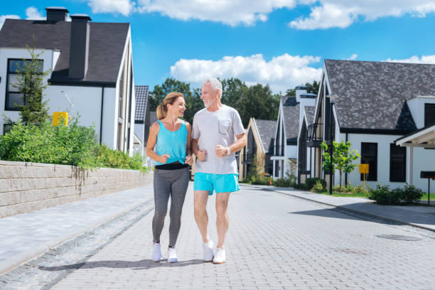 bärtige reife mann beitritt seine schöne schlanke frau laufen am morgen - immunsystem stärken stock-fotos und bilder