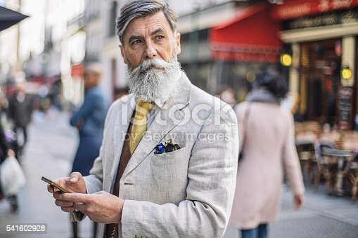 Bearded mature man texting at the streets of Paris.