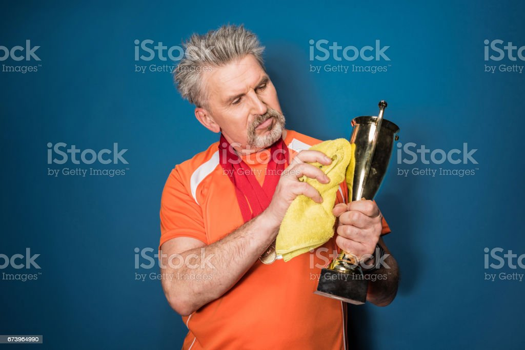 Bearded mature sportsman cleaning trophy cup isolated on blue royalty-free stock photo
