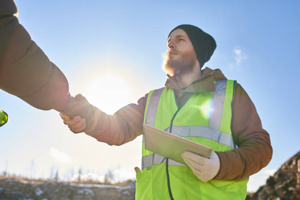 Bearded Miner Shaking Hands with Foreman Low angle portrait of bearded industrial worker wearing reflective jacket shaking with partner hands outdoors against cold blue sky frontier field stock pictures, royalty-free photos & images