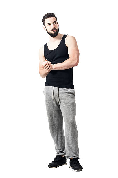 bearded muscular athlete with clasped hands looking up pensive - sweatpants stock-fotos und bilder