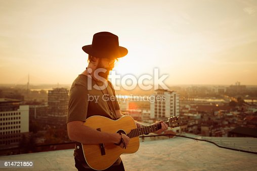 istock bearded musician playing the guitar on the roof 614721850