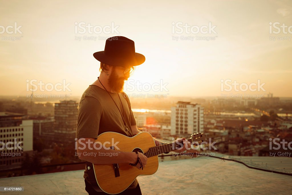 bearded musician playing the guitar on the roof stock photo