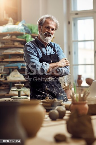 istock Bearded Old craftsman in pottery workshop 1094717634