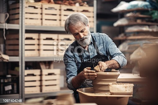 Bearded Old craftsman in pottery workshop