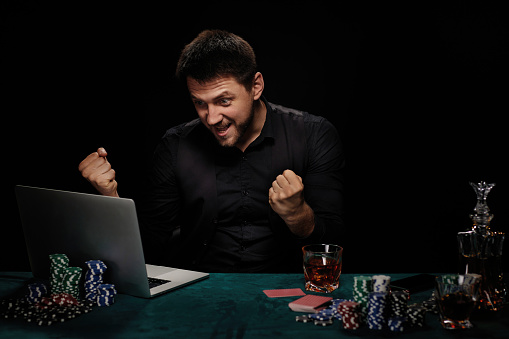 handsome bearded online casino player man celebrating victory in online casino. gambler looking at laptop