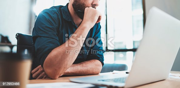 912969272istockphoto Bearded pensive man working at sunny office on laptop while sitting at wooden table.Businessman reports on notebook computer.Blurred background,horizontal. 912953466
