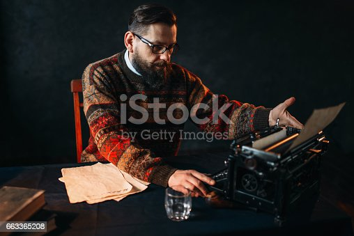 655113470istockphoto Bearded poet in glasses typing on typewriter 663365208