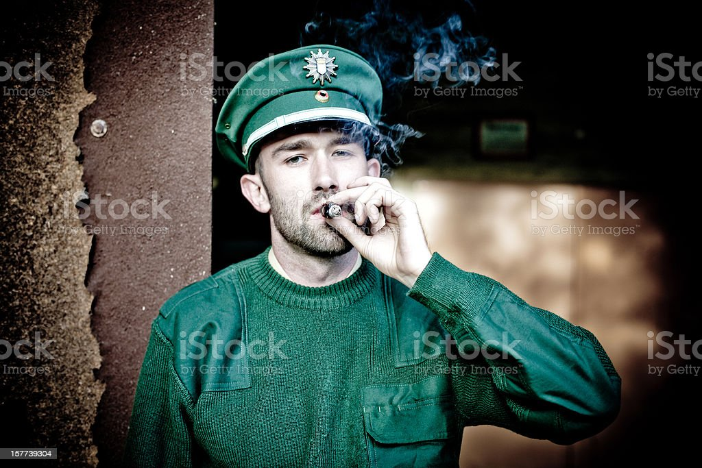 bearded policeman wears a green uniform and smokes a cigar stock photo