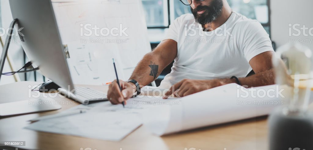 Bearded professional architect wearing eye glasses working at modern loft studio-office with desktop computer.Blurred background. Horizontal.Cropped. stock photo