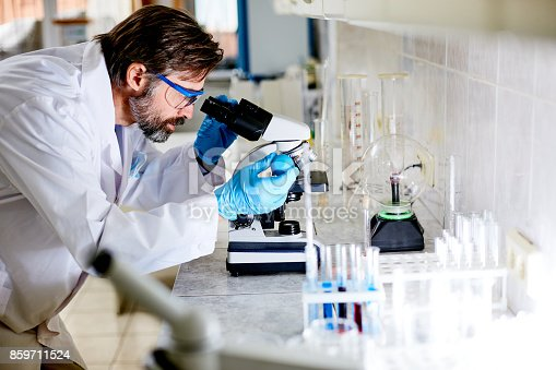 istock Bearded Researcher Using Microscope 859711524