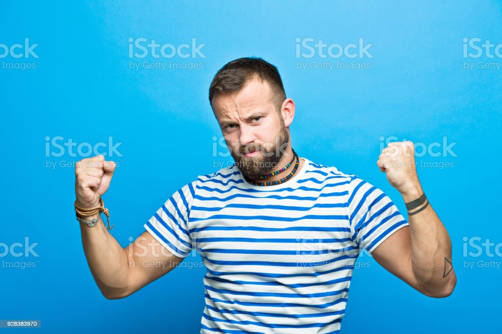 Bearded sailor flexing his muscles Portrait of bearded man wearing striped t-shirt flexing his muscles, looking at camera. Studio shot, blue background. 30-34 Years Stock Photo