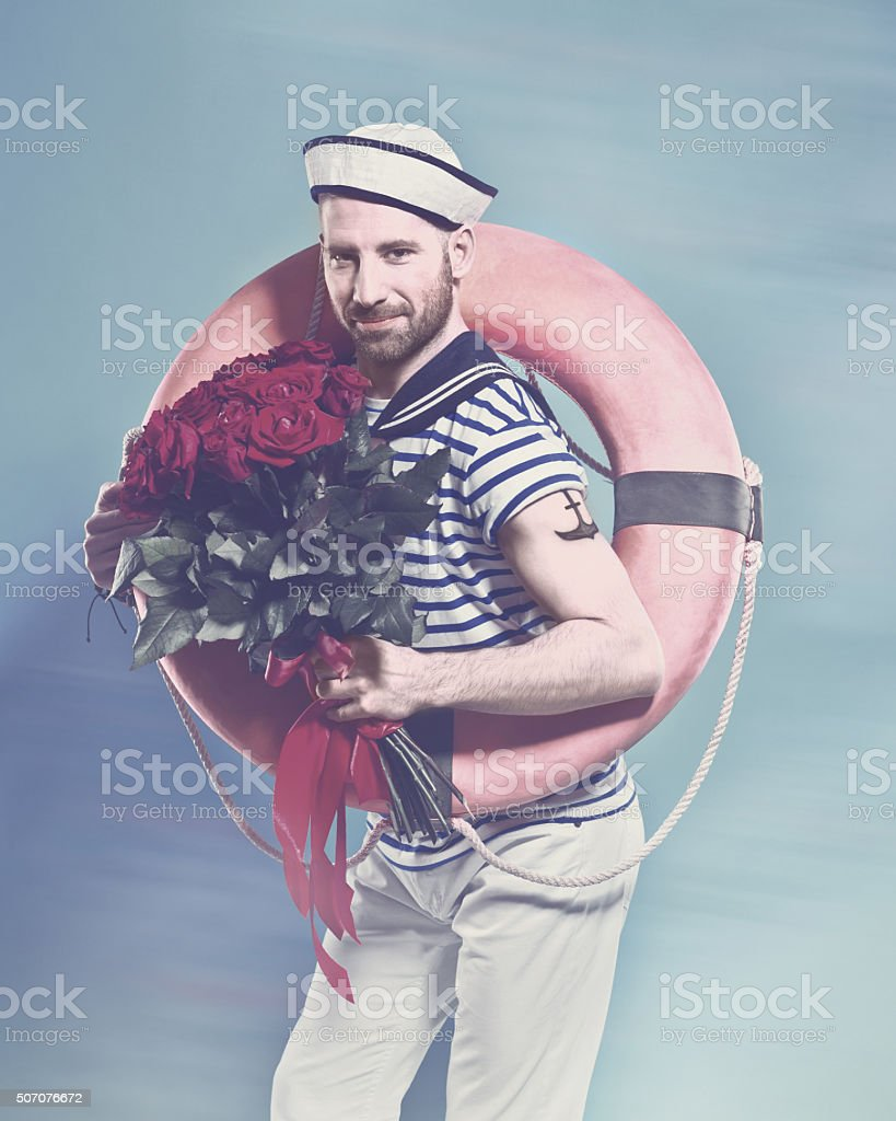 Bearded sailor holding lifebuoy and bunch of roses Summer portrait of bearded sailor man wearing white and blue striped t-shirt and sailor hat, holding lifebuoy on shoulder and bunch of roses in hand, smiling at camera. Standing against blue background. Studio shot, one person.  Adult Stock Photo