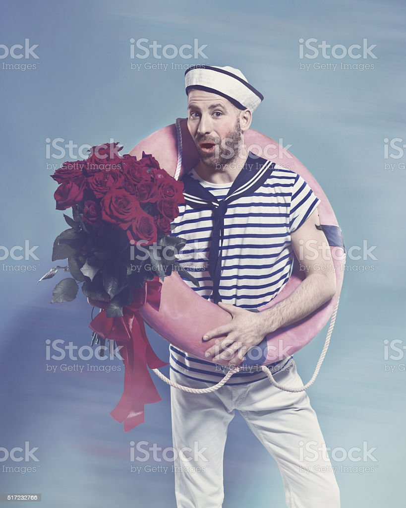 Bearded sailor holding lifebuoy and bunch of roses Summer portrait of bearded sailor man wearing white and blue striped t-shirt and sailor hat, holding lifebuoy on shoulder and bunch of roses in hand, staring at camera. Standing against blue background. Studio shot, one person.  Adult Stock Photo