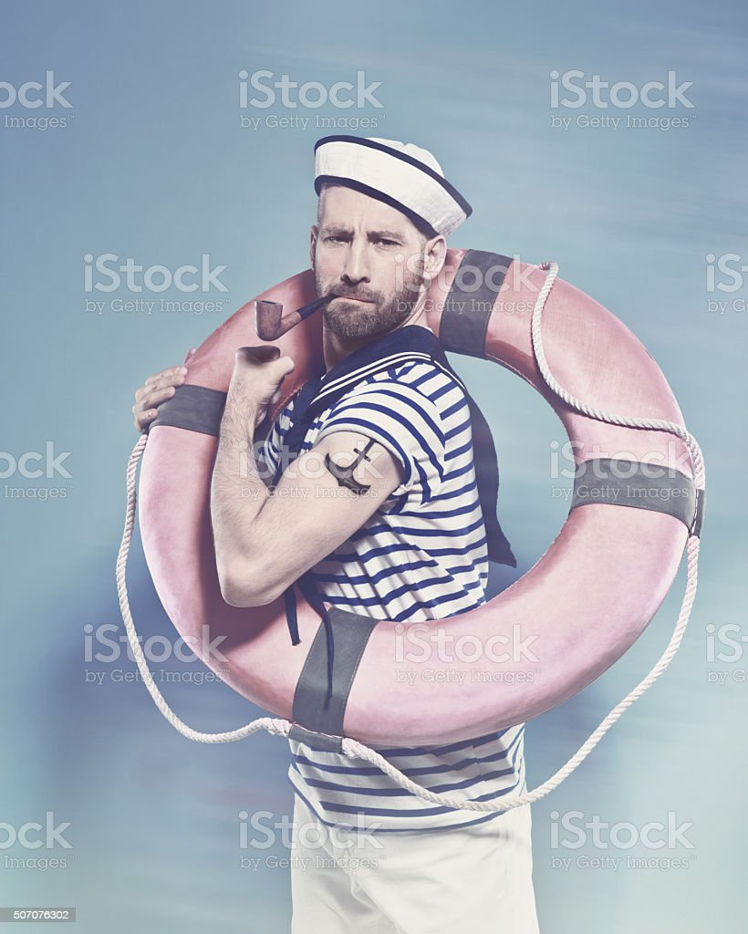 Bearded sailor holding lifebuoy and smoking pipe Summer portrait of bearded sailor man wearing white and blue striped t-shirt and sailor hat, holding lifebuoy on shoulder, flexing her arm with tatoo on shoulder and smoking pipe. Standing against blue background. Studio shot, one person.  Adult Stock Photo