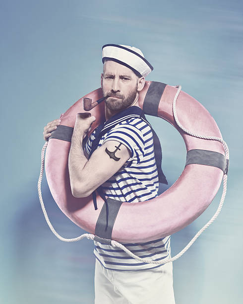 Bearded sailor holding lifebuoy and smoking pipe Summer portrait of bearded sailor man wearing white and blue striped t-shirt and sailor hat, holding lifebuoy on shoulder, flexing her arm with tatoo on shoulder and smoking pipe. Standing against blue background. Studio shot, one person.  anchor athlete stock pictures, royalty-free photos & images