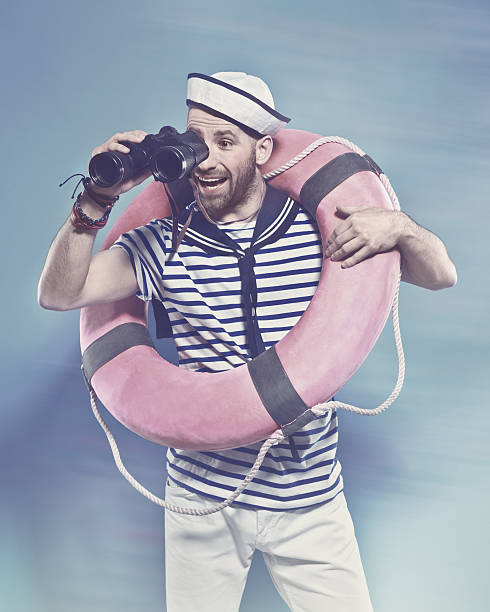 Bearded sailor holding lifebuoy, looking through binoculars Summer portrait of bearded sailor man wearing white and blue striped t-shirt and sailor hat, holding lifebuoy on shoulder and looking through binoculars. Standing against blue background. Studio shot, one person.  sailor suit stock pictures, royalty-free photos & images