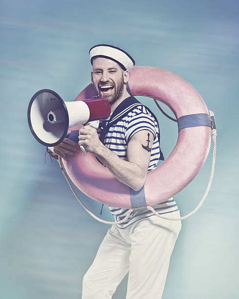 Bearded sailor holding lifebuoy, shouting into megaphone Summer portrait of bearded sailor man wearing white and blue striped t-shirt and sailor hat, holding lifebuoy on shoulder and screaming into megaphone. Standing against blue background. Studio shot, one person.  sailor suit stock pictures, royalty-free photos & images