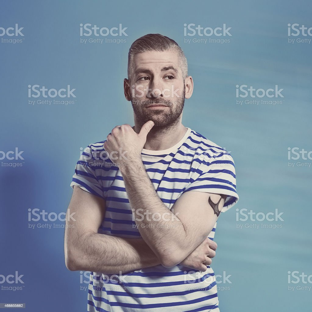 Bearded sailor man in stripped outfit Portrait of pensive bearded sailor man with anchor tatoo on shoulder wearing white and blue striped clothing. Standing with hand on chin against blue background, looking away. Studio shot, one person. 2015 Stock Photo