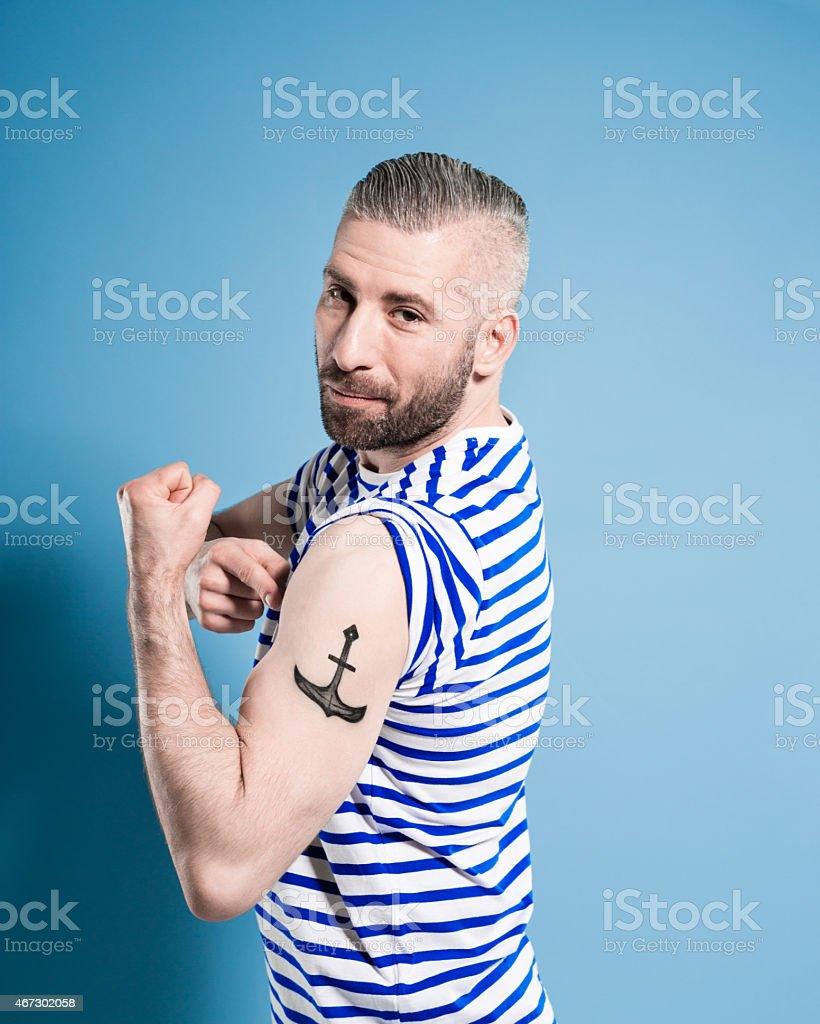Bearded sailor man showing his anchor tatoo Portrait of confident bearded sailor man wearing white and blue striped clothing flexing his bicep and showing anchor tatoo. Standing against blue background, looking at camera. Studio shot, one person. 2015 Stock Photo