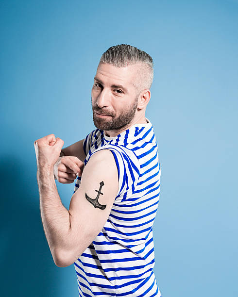 Bearded sailor man showing his anchor tatoo Portrait of confident bearded sailor man wearing white and blue striped clothing flexing his bicep and showing anchor tatoo. Standing against blue background, looking at camera. Studio shot, one person. sailor stock pictures, royalty-free photos & images
