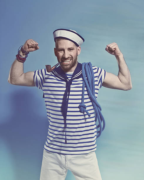 Bearded sailor man smoking pipe and flexing his arms Portrait of confident bearded sailor man wearing white and blue striped clothing and sailor hat, holding blue rope on shoulder. Standing against blue background, smoking a pipe and flexing his arms. Studio shot, one person. sailor suit stock pictures, royalty-free photos & images