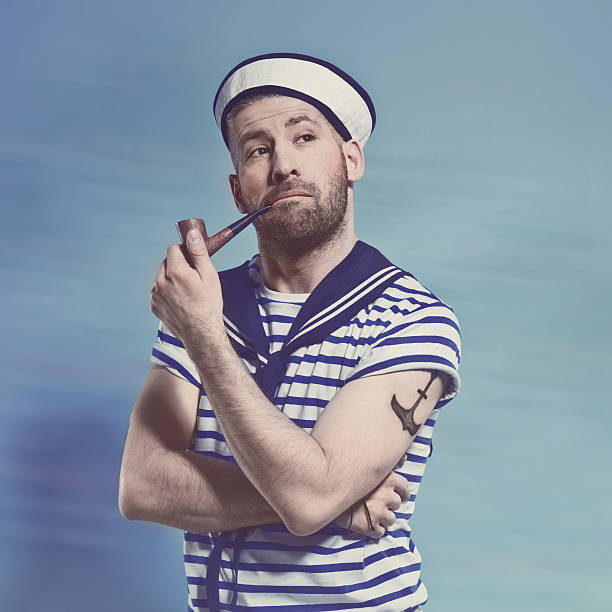 Bearded sailor man smoking pipe Portrait of pensive bearded sailor man wearing white and blue striped clothing and sailor hat. Standing against blue background and smoking a pipe. Studio shot, one person. sailor suit stock pictures, royalty-free photos & images