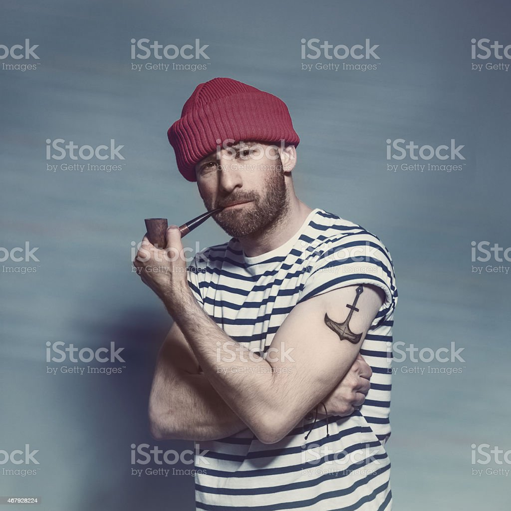 Bearded sailor man smorking pipe Portrait of confident bearded sailor man with anchor tatoo on shoulder wearing white and blue striped clothing and red wool cap. Standing against blue background, looking at camera and smoking pipe. Studio shot, one person. 2015 Stock Photo