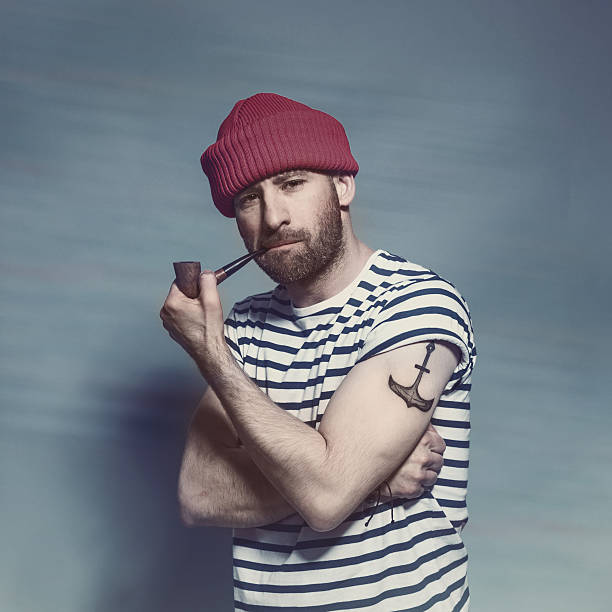 Bearded sailor man smorking pipe Portrait of confident bearded sailor man with anchor tatoo on shoulder wearing white and blue striped clothing and red wool cap. Standing against blue background, looking at camera and smoking pipe. Studio shot, one person. sailor stock pictures, royalty-free photos & images