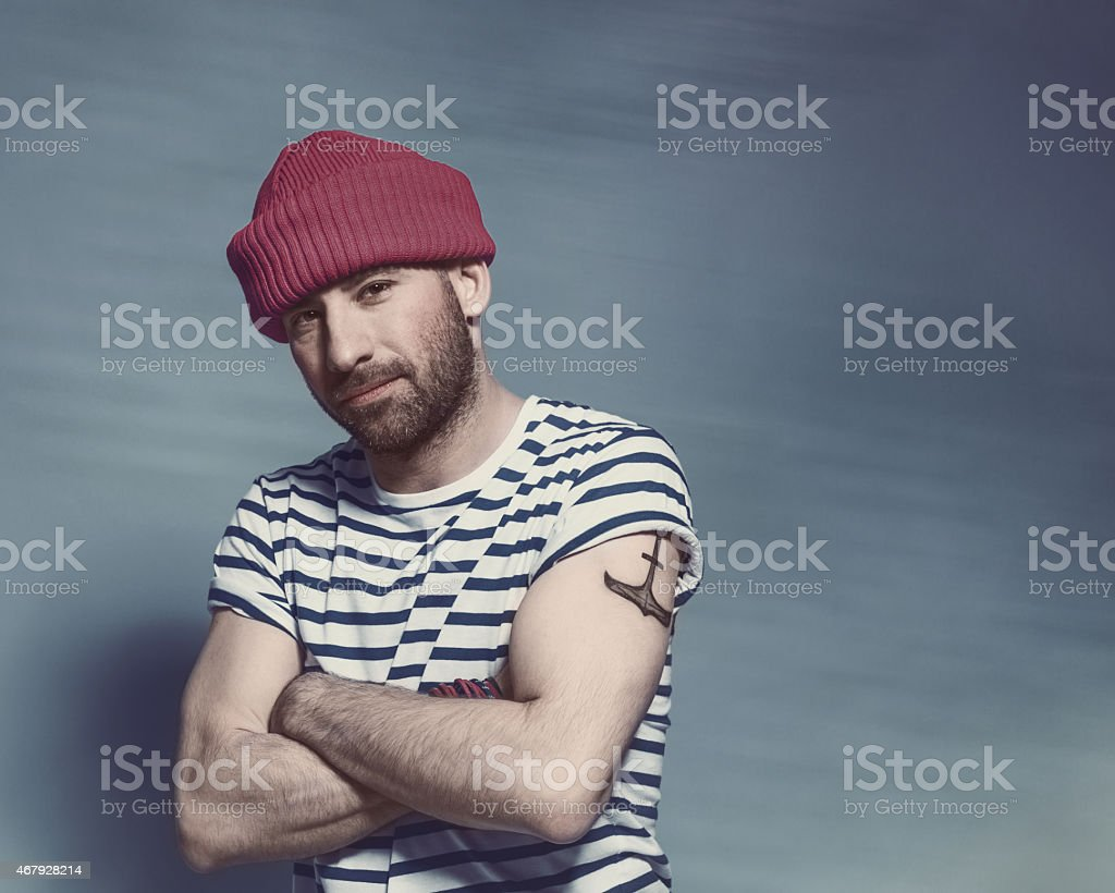 Bearded sailor man wearing striped t-shirt and wool cap Portrait of confident bearded sailor man with anchor tatoo on shoulder wearing white and blue striped clothing and red wool cap. Standing with arms crossed against blue background, looking at camera. Studio shot, one person. 2015 Stock Photo