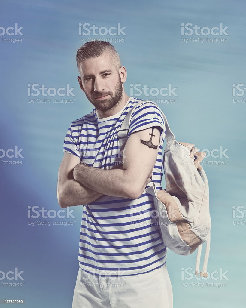 Bearded sailor man wearing striped t-shirt Portrait of confident bearded sailor man with anchor tatoo on shoulder wearing white and blue striped clothing, holding backpack. Standing with arms crossed against blue background, looking at camera. Studio shot, one person. 2015 Stock Photo