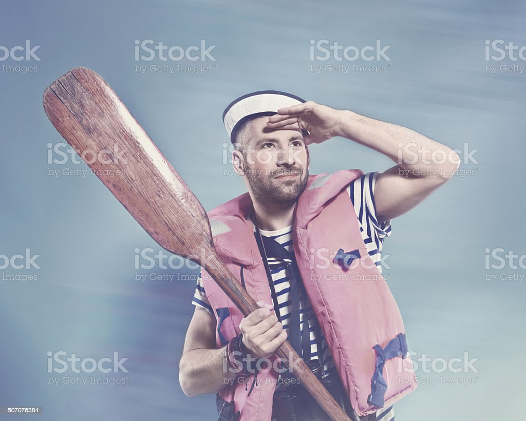 Bearded sailor wearing life jacket holding paddle Summer portrait of bearded sailor man wearing white and blue striped t-shirt, sailor hat and life jacket holding paadle in hand and looking away. Standing against blue background. Studio shot, one person.   Adult Stock Photo