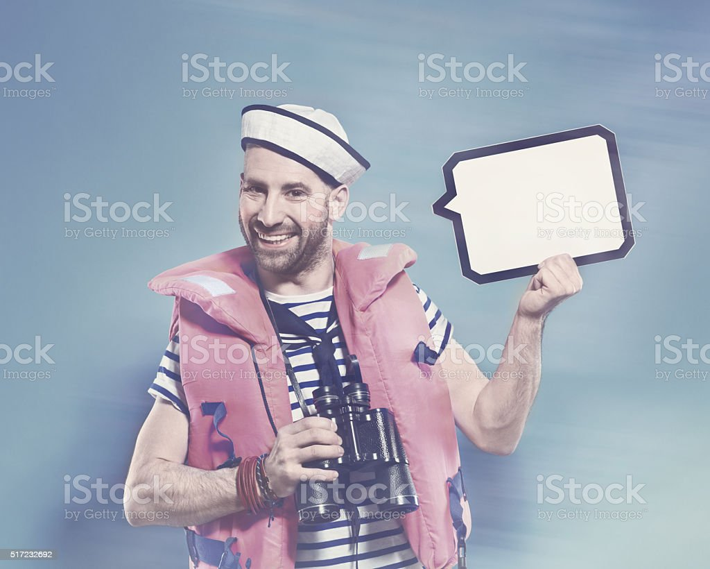 Bearded sailor wearing life jacket, holding speech bubble Happy bearded sailor man wearing life jacket and binoculars, holding speech bubble in hand and smiling at camera. Standing against blue background. Studio shot, one person.  Adult Stock Photo