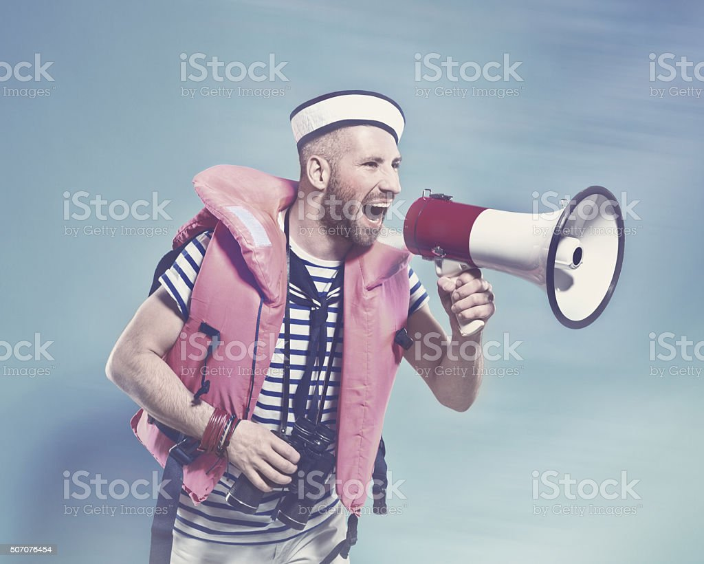 Bearded sailor wearing life jacket shouting into megaphone Summer portrait of bearded sailor man wearing white and blue striped t-shirt, sailor hat and life jacket shouting into megaphone. Standing against blue background. Studio shot, one person.   Adult Stock Photo