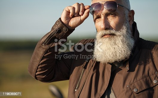Portrait of a bearded senior man outdoors. Old biker portrait.
