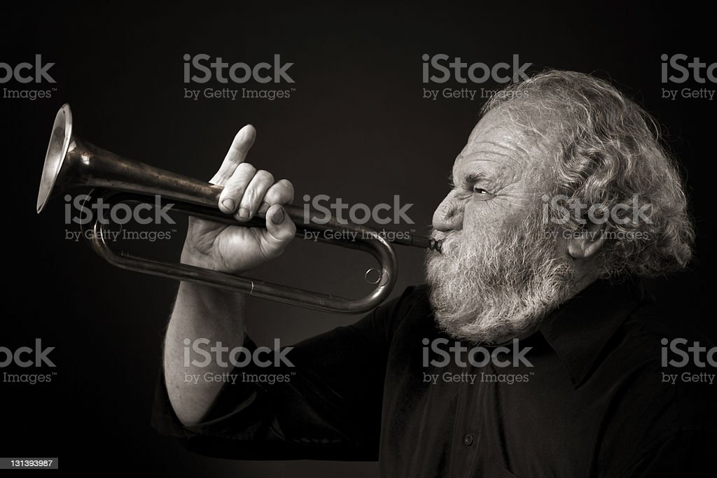 Bearded senior musician blowing hard on bugle royalty-free stock photo