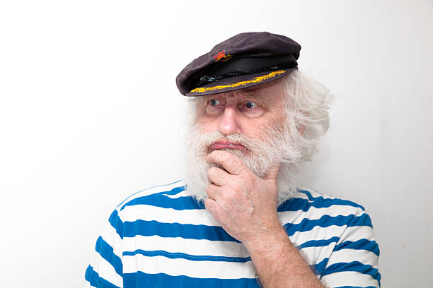 b79ac4cd37dc7 bearded senior sailor with cap and striped jersey stock photo